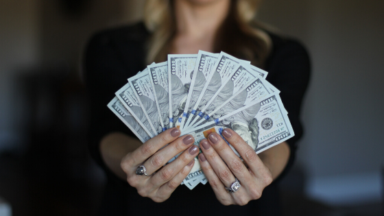 A woman in business attire holding a lot of money