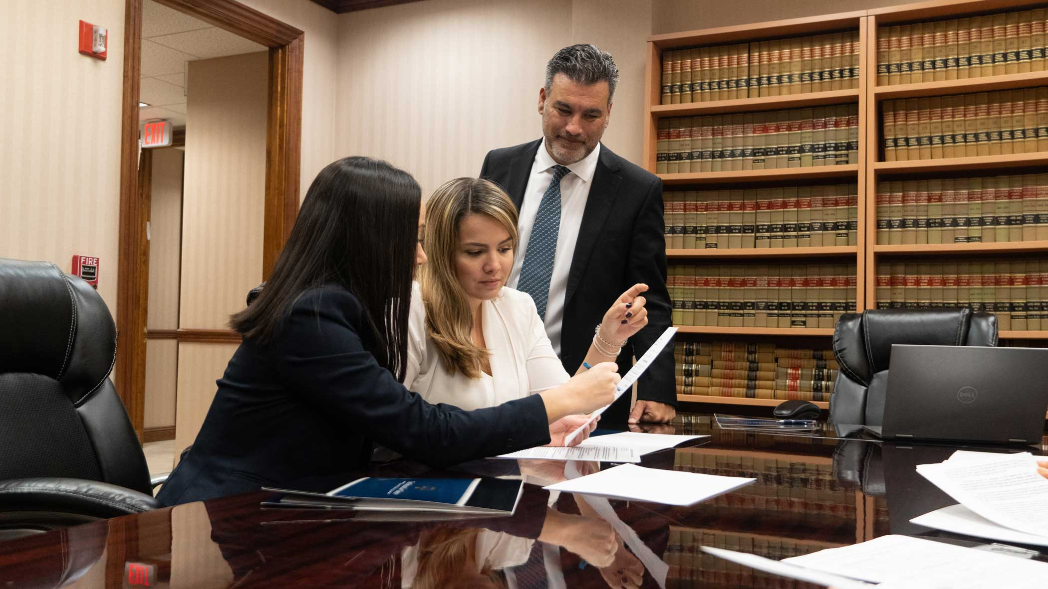 Two female lawyers are seating on a chair and the male lawyer is standing at their side, all are reviewing papers